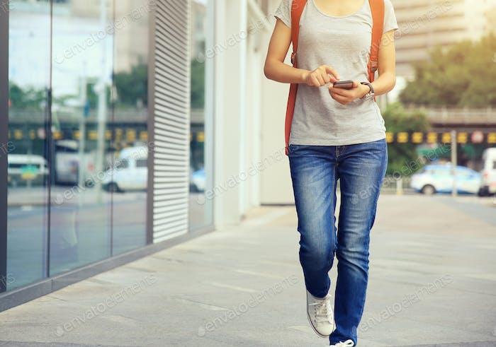 Mujer caminando y usar el teléfono Móvil en la calle de la Ciudad