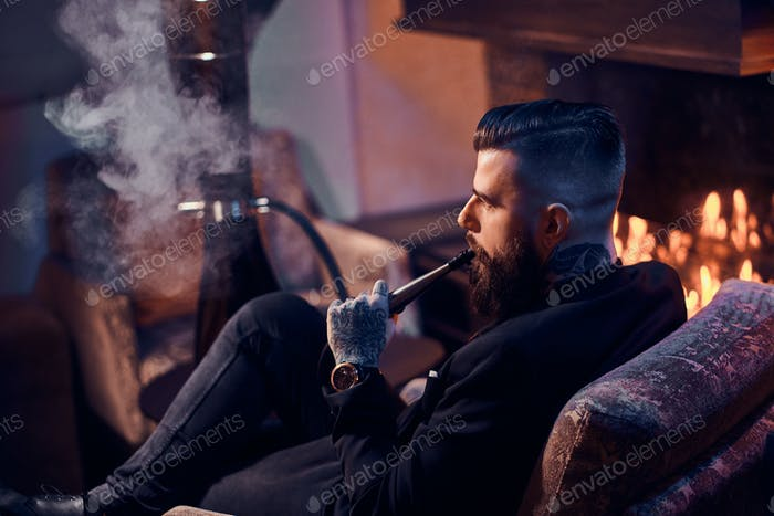 Bearded man is making nice misty vapour while relaxing near fireplace and smoking hookah.