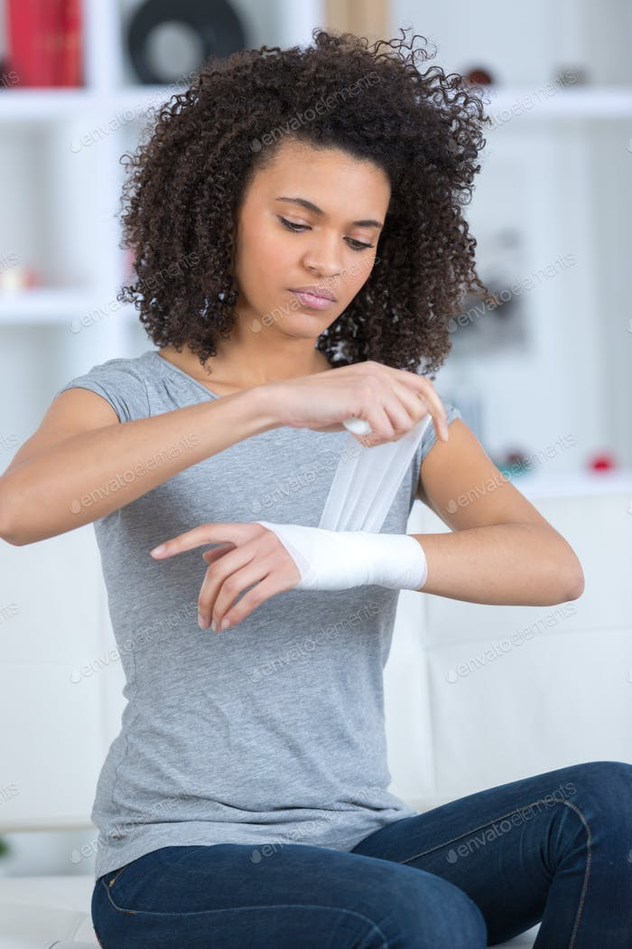 woman bandaging her wrist indoors