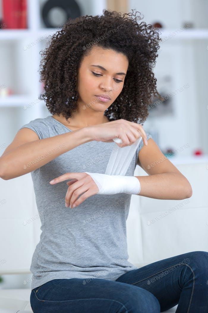 Frau Bandagieren ihr Handgelenk drinnen