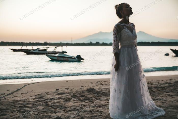 Schöne Braut tanzt am Strand