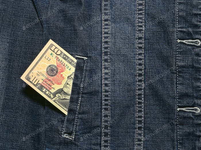 Ten american dollars in a pocket of a denim jacket