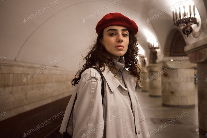 Gorgeous girl in trench coat and beret confidently looking in camera waiting train at underground