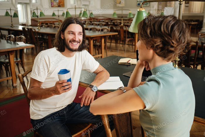 Handsome smiling male student joyfully talking with friend during study break in university library
