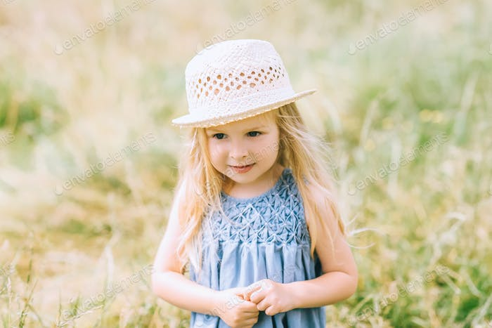 adorable blonde child in dress and straw hat