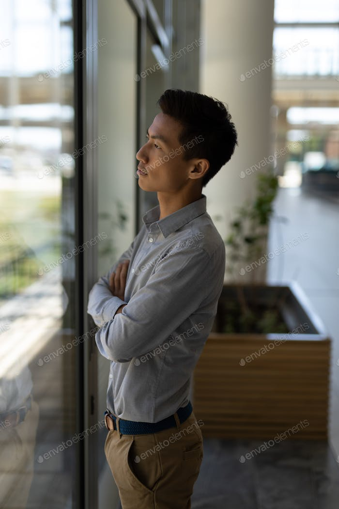 Side view of young Asian male executive standing with arms crossed in modern office. He is thinking