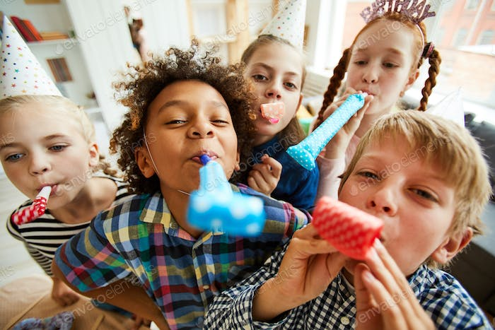 Happy Kids Blowing Party Horns