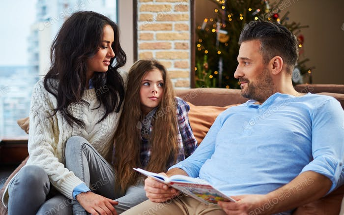 Father reading book to his cheerful family