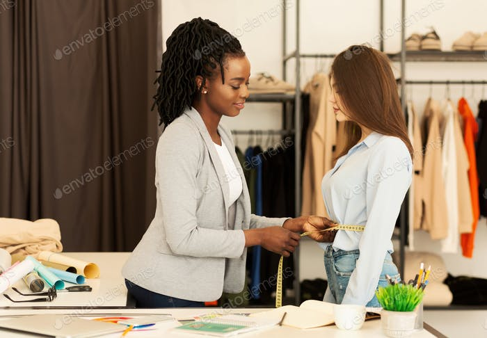 African American Tailor Measuring Woman's Waist Working In Clothing Atelier