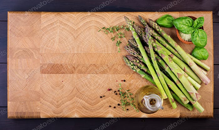 Fresh green asparagus on a rustic wooden table with copy space. Top view