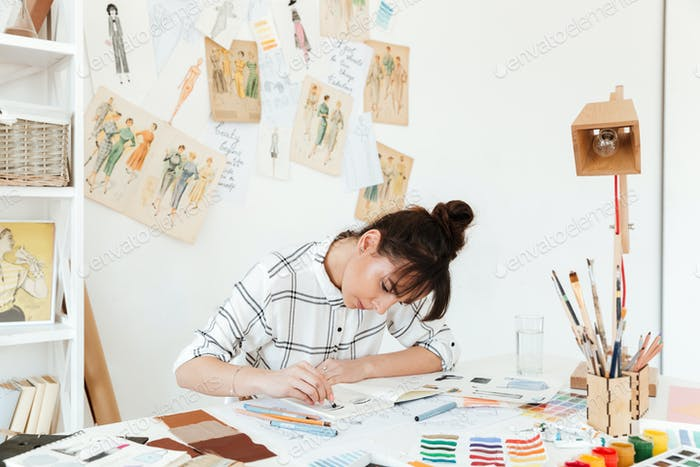 Picture of young concentrated woman fashion illustrator