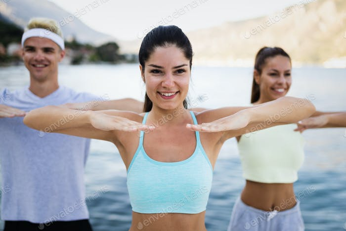 Group of happy people exercising outdoor. Sport, fitness, friendship and healthy lifestyle concept