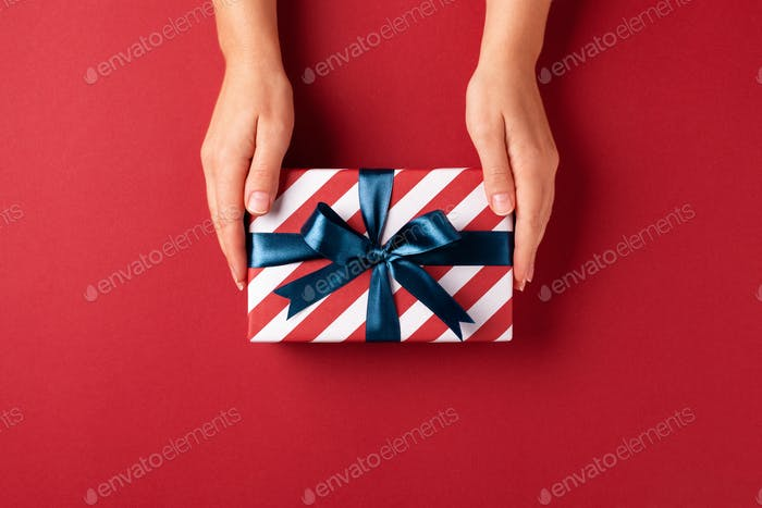Female`s Hands Holding Gift Box on Red Background.