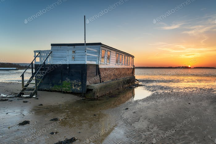 Sunset over an old wooden houseboat on the shore of Bramble Bush