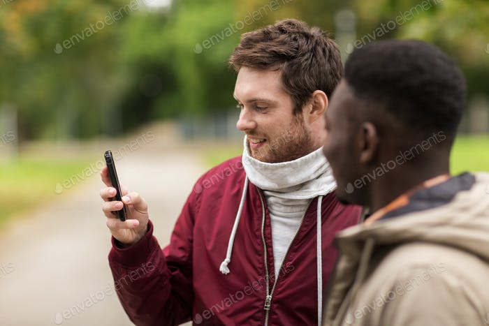 happy friends with smartphone outdoors