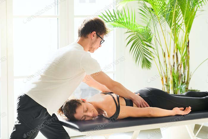 Young osteopath doing a lumbosacral evaluation