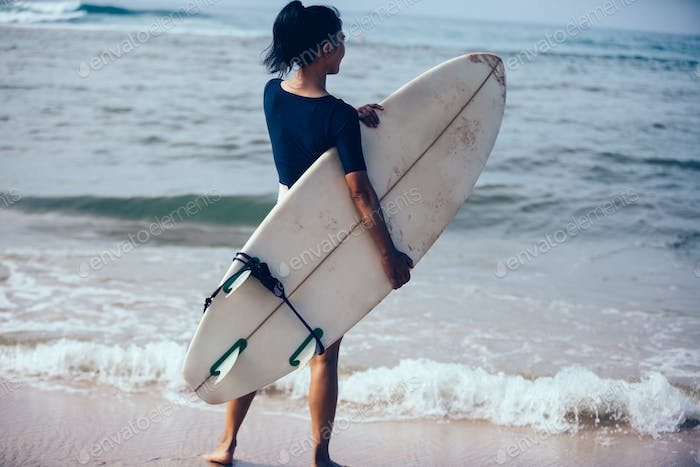 Surfer woman with surfboard the beach