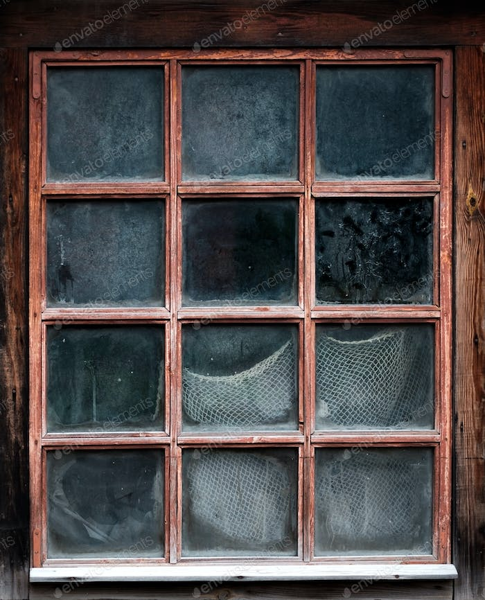 The window of an old,wooden farm house with net