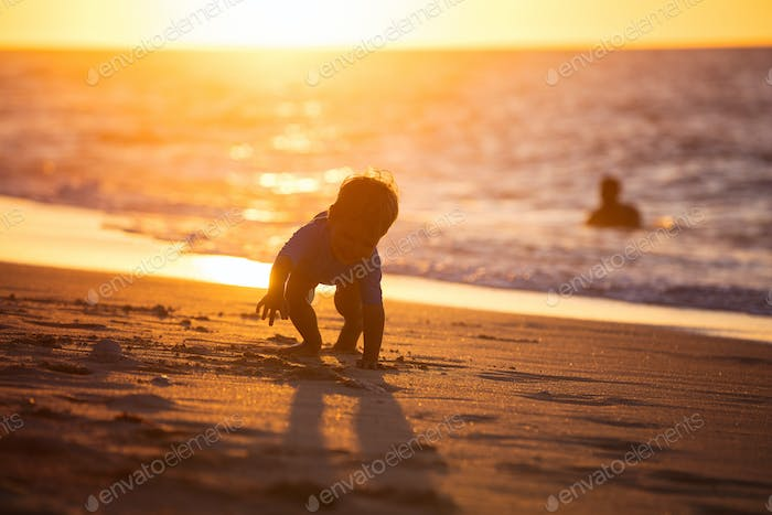 Happy little boy playing on beach. Sunset light