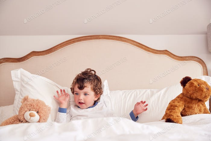 Young Boy Lying In Parents Bed With Cuddly Teddy Bear Toys
