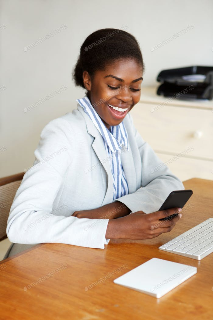 happy young african american businesswoman sitting at desk with cellphone