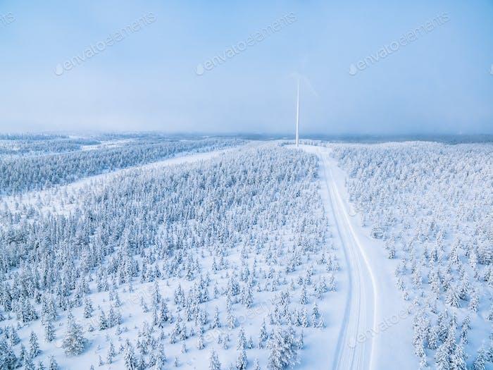 Luftaufnahme der Windmühle im Winterwald mit Schneestraße in Finnland.