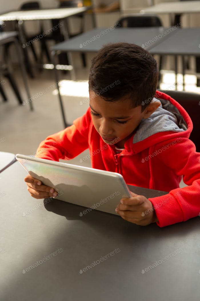 Schoolboy using digital tablet at desk in classroom at elementary school
