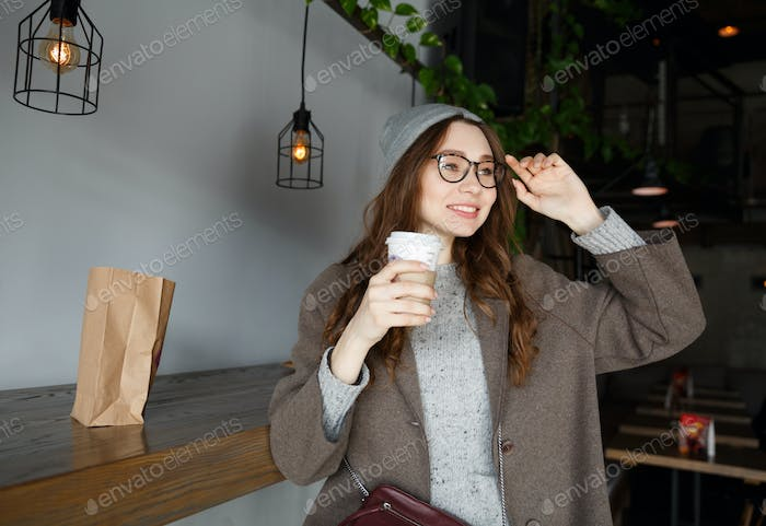 Cheerful charming young woman sitting and drinking coffee in cafe
