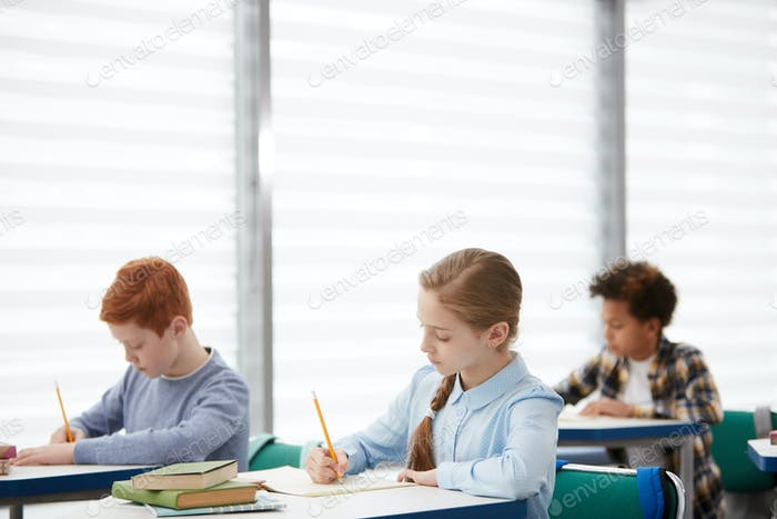 Group of Children Writing in Class