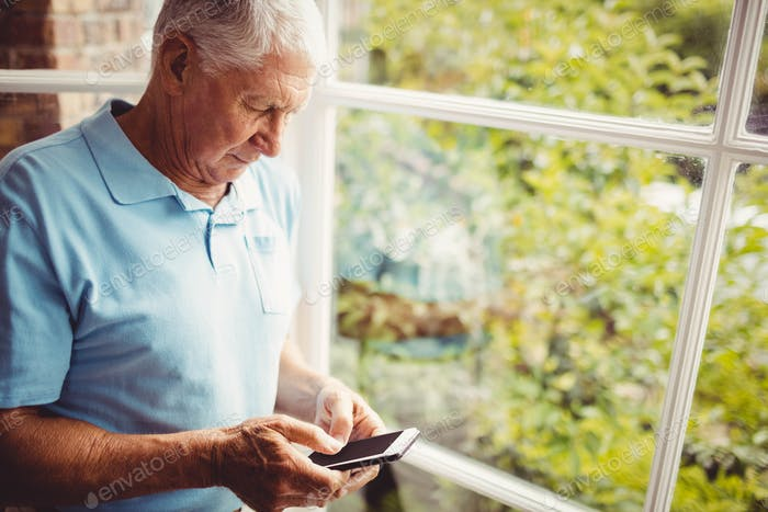 Senior man next to the window using smartphone at home