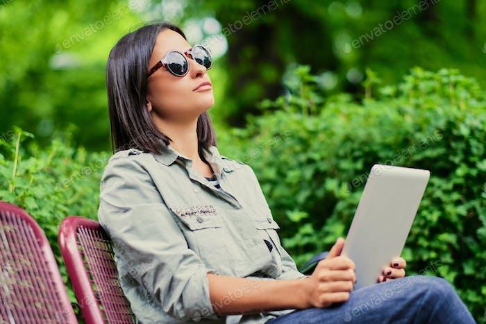 Brünette weiblich sitzt auf einer Bank und hält Tablet-PC in einem Sommerpark.