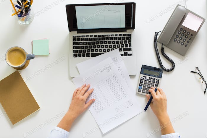 hands with calculator and papers at office table