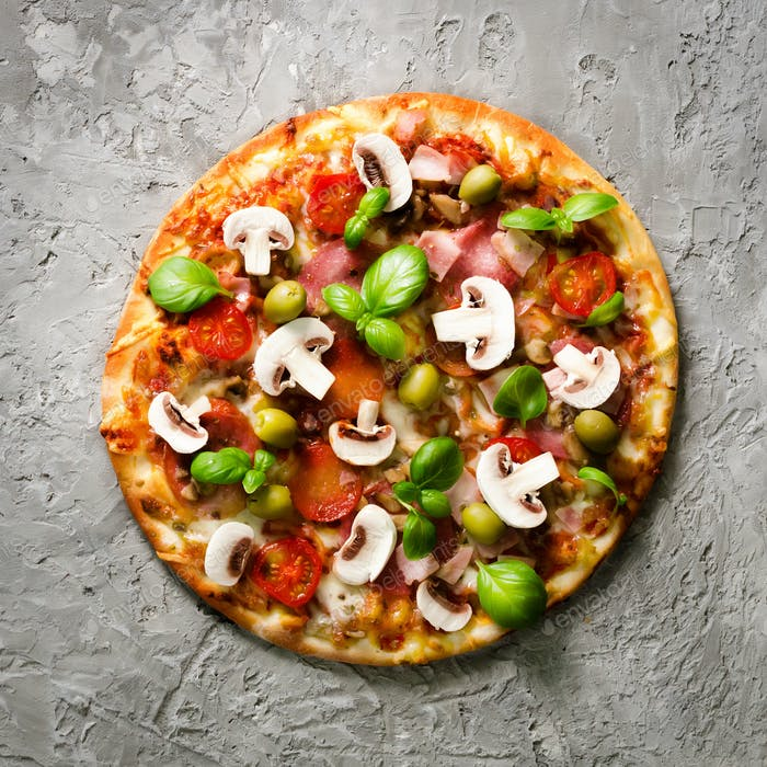 Fresh italian pizza with mushrooms, ham, tomatoes, cheese on on grey concrete background. Copy space