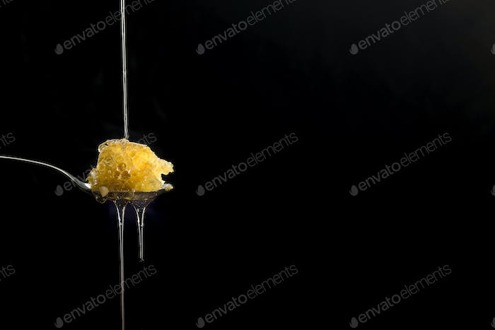 Organic raw honeycombs on spoon with honey drops, pure natural sweet goodness on black background.