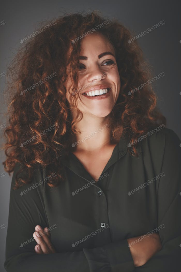 Confident young businesswoman standing against a gray background