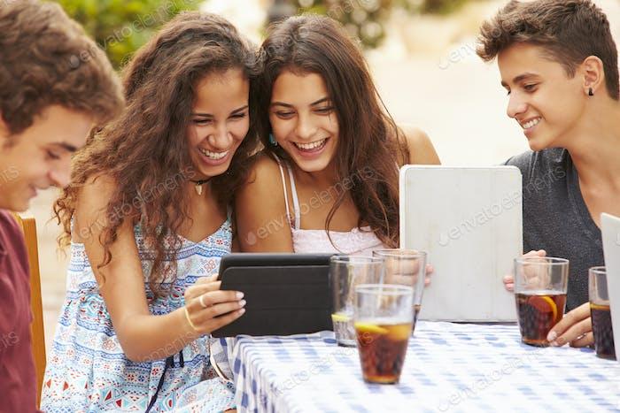 Teenager-Freunde sitzen im Caf' mit digitalen Tablets