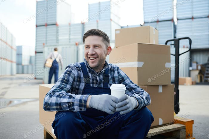 Cheerful manual worker at outdoor storage container area