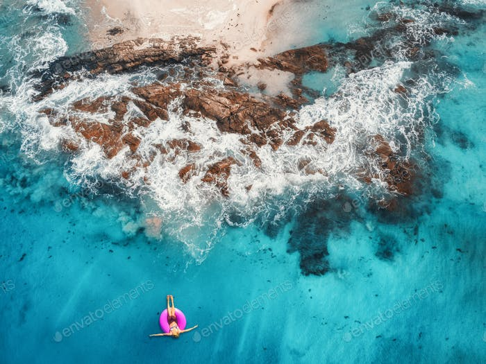 Aerial view of young woman swimming on the pink swim ring in the transparent turquoise sea