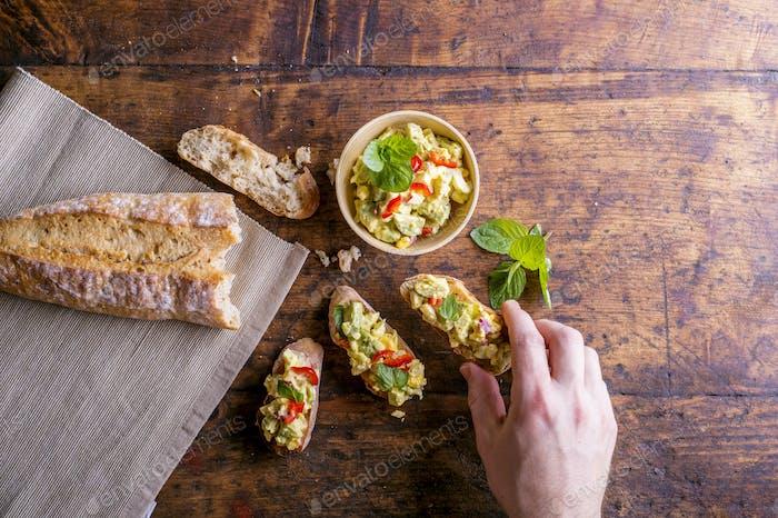 Man taking avocado spread on bruschetta slices, wooden table
