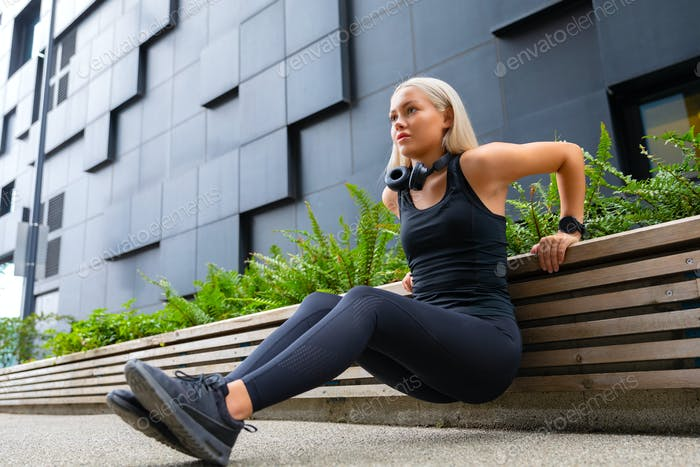 Focused Woman Doing Heavy Triceps Dips Outdoor in the City