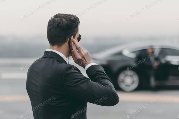 handsome bodyguard standing and listening message with security earpiece on helipad