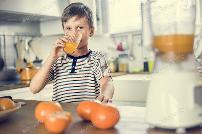 Young Caucasian boy drinking orange juice