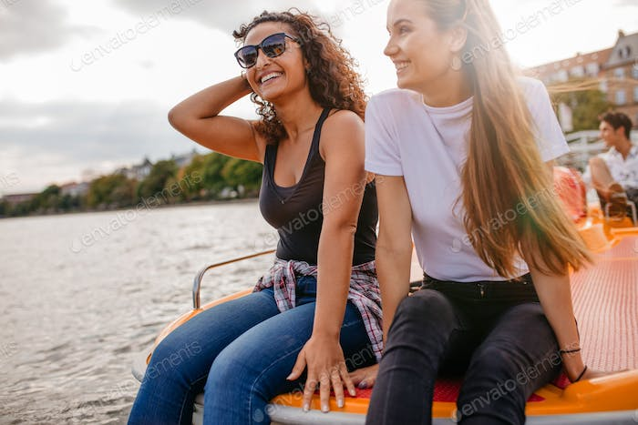 Friends relaxing on pedal boat in lake