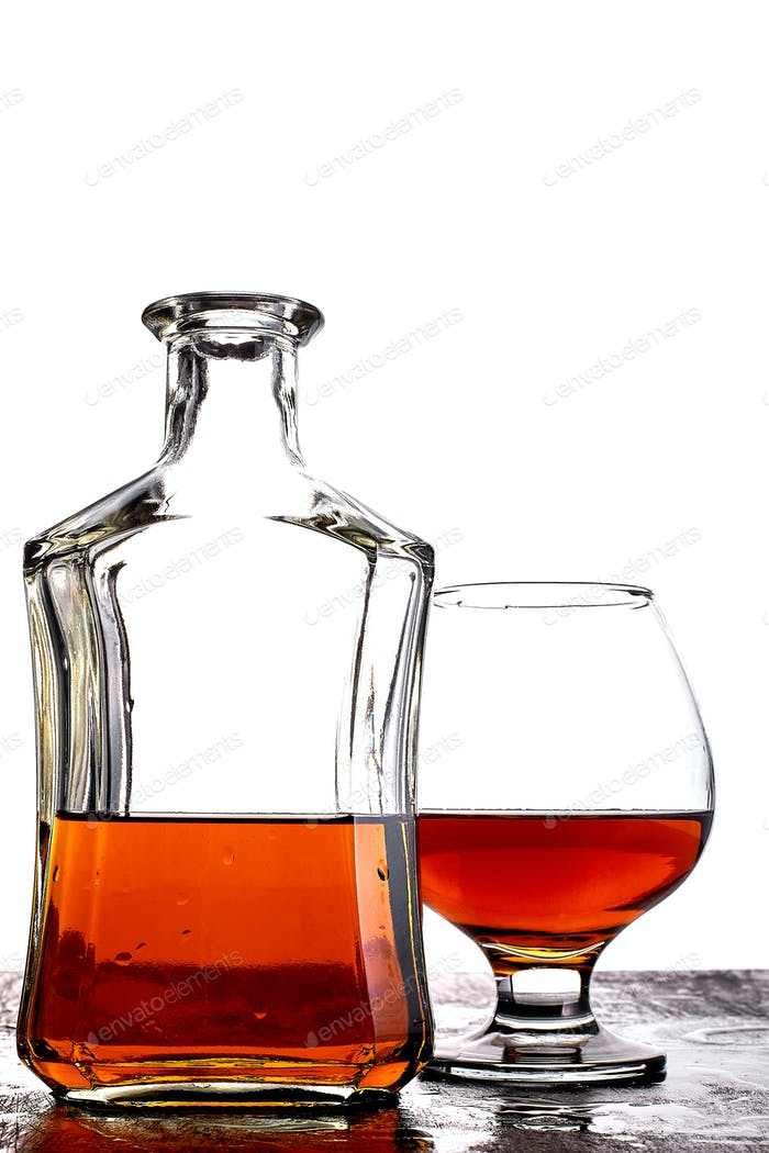 Glass of splash whiskey with bottle.