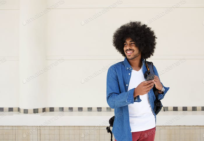 Cool guy smiling with bag and cellphone
