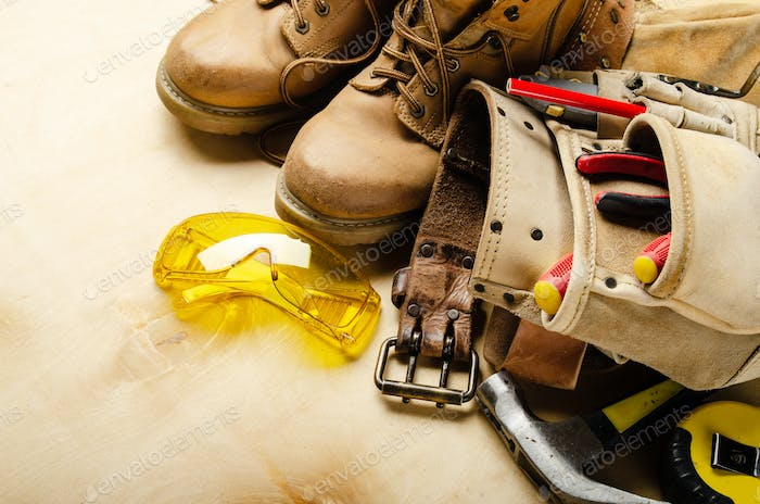 Construction concept background of toolbelt yellow boots goggles ant tools on plywood
