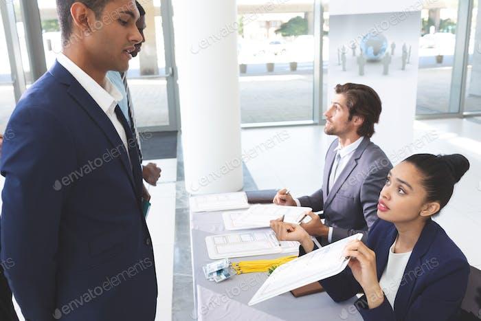Seitenansicht von diversen Geschäftsleuten, die am Konferenzregistrierungstisch in der Bürolobby einchecken