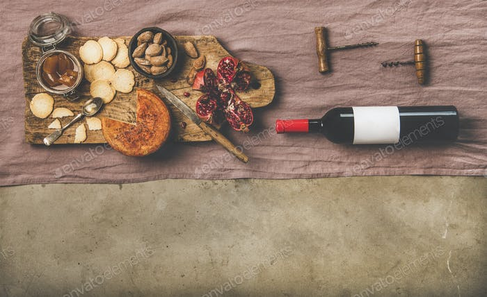 Wine bottle, vintage corkscrews and appetizers on board, copy space