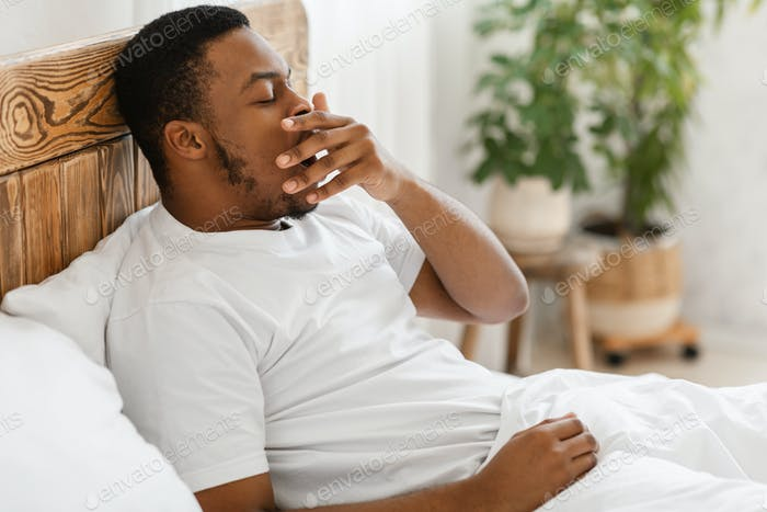Sleepy African American Guy Yawning Waking Up In Bed Indoors