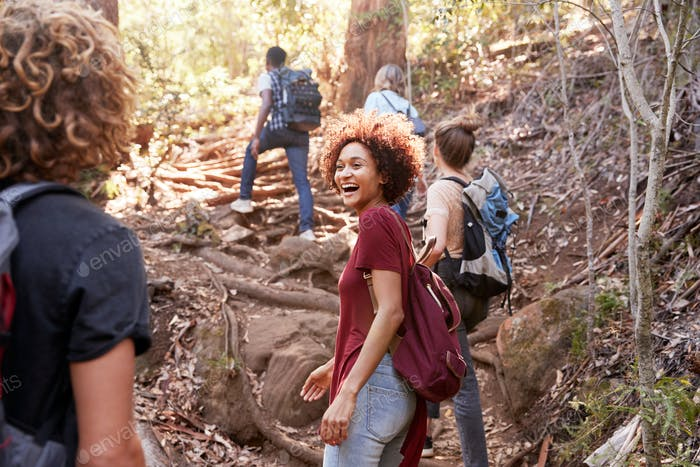 Group of millennial  friends hiking uphill on a forest trail, three quarter length